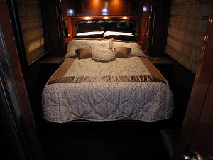 Queen size bed in the rear stateroom along with a makeup table, TV/audio-visual system, with tracking satellite, second lavatory, and shower.