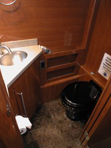 One of the two lavatories in the coach. This one is in the galley area and has a toilet, sink, and storage.