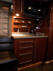 The galley is located on the passenger side of the coach in the front lounge. There is a hard surface countertop, a drop down garbage chute, a sink, Microwave, pullout cooktop in a drawer, and a refrigerator/freezer