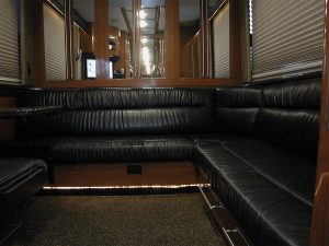 a spacious rear lounge with leather seats, an ice box, mirrored closets along the back wall, entertainment center, and a booth