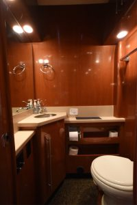 lavatory, tile flooring, toilet, sink with countertop and wash basin, storage cabinets, mirror