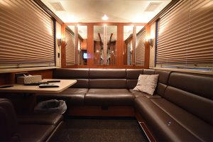 Rear lounge, L-shaped leather sofa and booth, mirrored closets along the back wall, A second Direct Tv receiver with satellite in-motion tracking, surround sound audio-visual system,