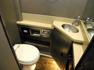 There are two lavatories in this coach. This is a photo of the one in the front lounge. Hard surface countertop with sink, Toilet, tile flooring, and storage