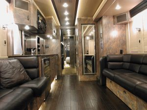 2006 Prevost XLII front lounge. Two leather sofas, wood flooring, Galley, entertainment center, Day/night shades, galley, Lavatory, and storage.