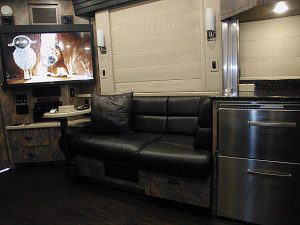 Front lounge small leather sofa located between the galley and the entertainment center