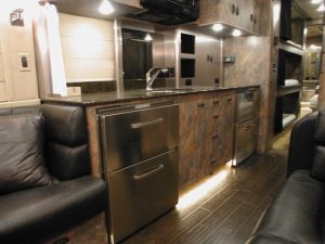 Galley with sink, cooktop, microwave, trash chute, lighting, and storage drawers