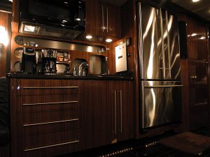 Full galley in the front lounge: convection microwave, Side by side stainless refrigerator, sink, storage cabinets with drawers, and cooktop