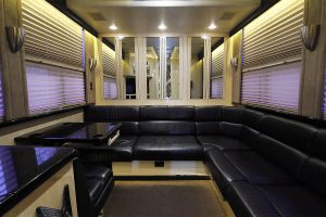 rear lounge: L-shaped leather sofa, Mirrored closets across the rear, and a booth highlight the rear lounge of this coach